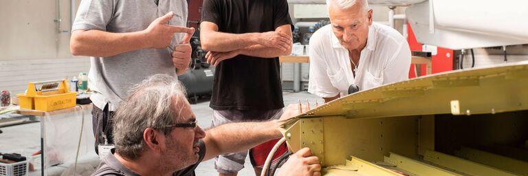 Die Flugzeugmechaniker (links) der Reparaturfirma zeigen Paraclub-Betriebsleiter Serge (Mitte) und Bruno Wirz (rechts) alle Einzelheiten.